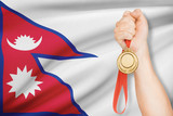 Medal in hand with flag - Federal Democratic Republic of Nepal