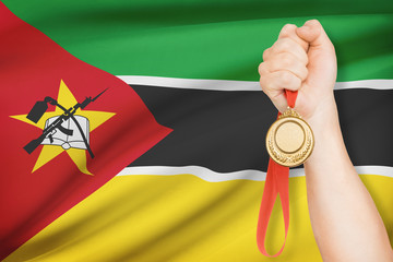 Medal in hand with flag on background - Republic of Mozambique