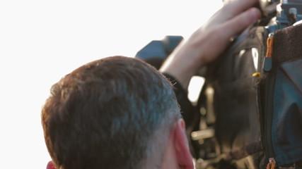 Cameraman working outdoors. Close-up