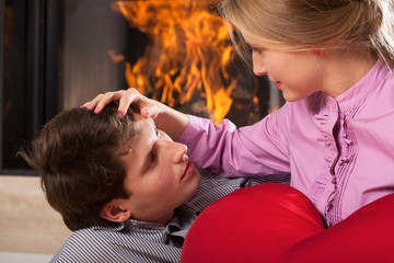 Caring wife with husband by fireplace