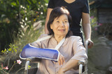 Asian senior woman with broken wrist on wheel chair