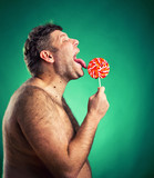Shirtless man licking lollipop candy