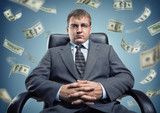 Young businessman in a chair with flying money