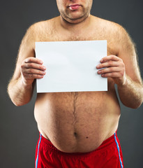 Fat man with blank card  in studio
