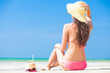 Happy young woman in straw hat and bikini with coconut on the