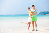 Couple in bright clothes on tropical beach in Thailand