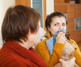 woman caring for  adult daughter has cough