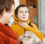 Woman giving glass of water to unwell friend