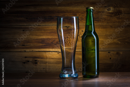 Beer bottle and empty glass of beer