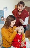 woman with mature mother caring for sick toddler