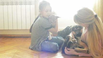 two girls playing on the floor with two dogs