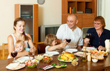 Portrait of happy family together over dining table eating chick