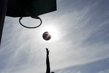 Silhouette of a basketball player scoring