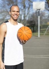 Portrait of a male basketball player on an outdoor court