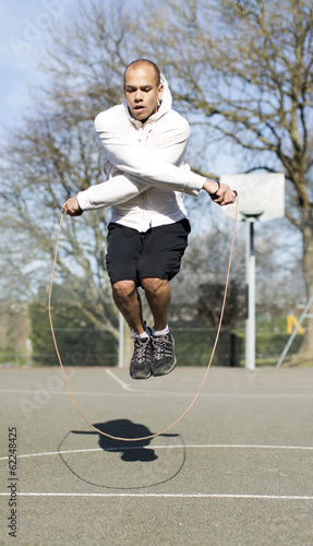 Man skipping fancily outdoors on a basketball court