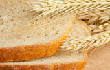 sliced bread and wheat ears on the wooden table background