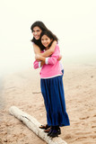 Sisters hugging on foggy beach