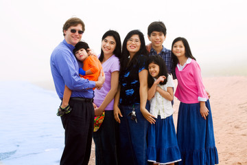 Multiracial family of seven on foggy beach
