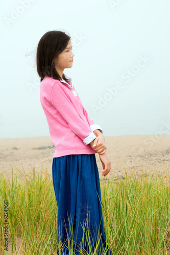 Young girl quietly standing on misty foggy field