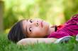 Little girl lying on grass