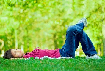 Little girl lying on grass lawn sleeping ,