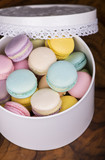 Pastel color macaroons in vintage round box on a wooden