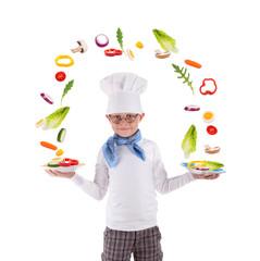 kleiner Koch balanciert frische Salatzutaten