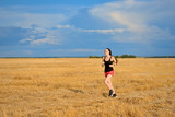 Young Woman Jogging in field
