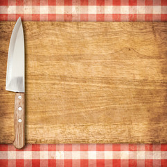 Cutting breadboard and knife over red grunge gingham tablecloth