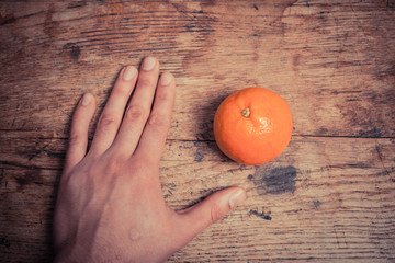 Hand and orange on table