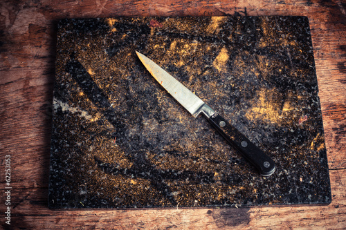 Knife and chopping board covered in spices