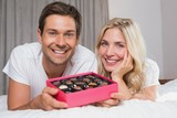 Young couple with candies resting in bed
