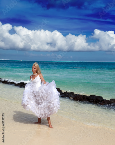 young beautiful woman in a dress of bride standing at sea edge..
