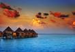 Leinwanddruck Bild - houses on piles on water at the time sunset
