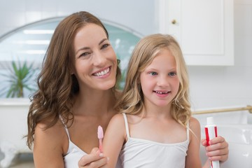 Mother and daughter with toothbrush and toothpaste