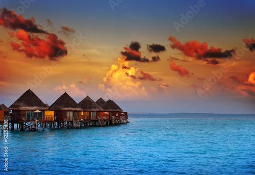 Leinwanddruck Bild houses on piles on water at the time sunset