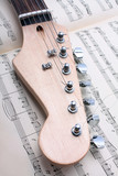 electric guitar fretboard and music sheet