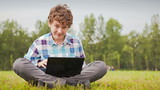 Young man sitting on a green meadow with a netbook