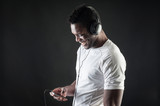 Black man listening to music with ear-phones against dark backgr