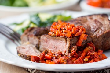 Grilled beef steak with salsa sauce dried tomatoes, red peppers