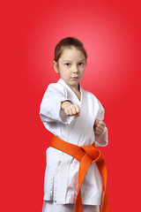 With orange belt serious sportwoman is hitting punch hand