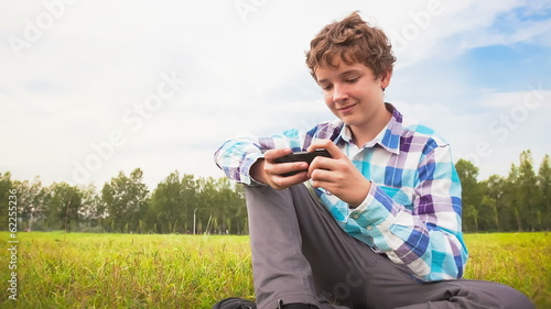 man sitting on a green meadow with a cellphone