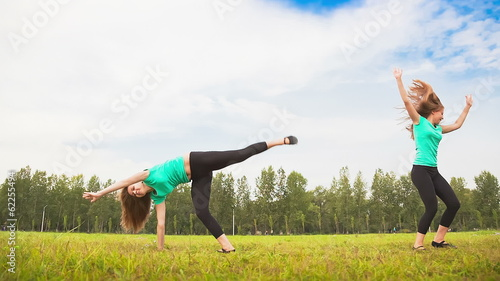 Young Woman Tumbling Wheel, acrobatics on a green glade
