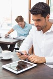 Concentrated man text messaging in coffee shop