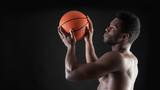 Portrait of confident young black man shirtless throwing basket