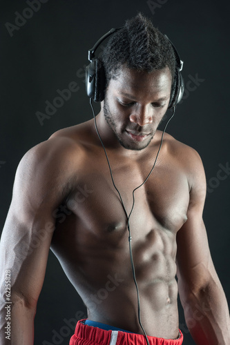 Black man with ear-phones against dark background.