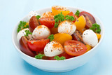 bowl of salad with mozzarella, fresh herbs and cherry tomatoes