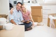 Couple using digital tablet amid boxes in new house