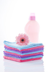 clean towels and laundry softener isolated on white