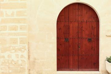 geschlossene rundbogentüre aus Holz in einer mediterranen Sands